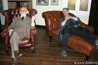 Sigmund Freud and Martin at Madame Tussauds in Vienna, in Austria. On the left side sits relaxed Sigmund Freud. Martin lies on the right side on a couch with mouth wide open and holds frantically with both hands his throat.